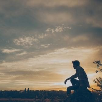 Boy sitting in field at dusk
