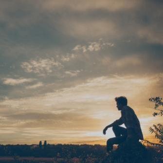 Boy sitting in field at dusk